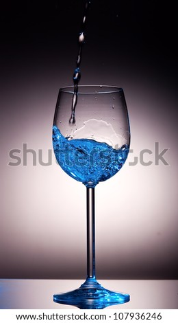 Clear liquid poured into crystal wine glass that have a blue tint - stock photo