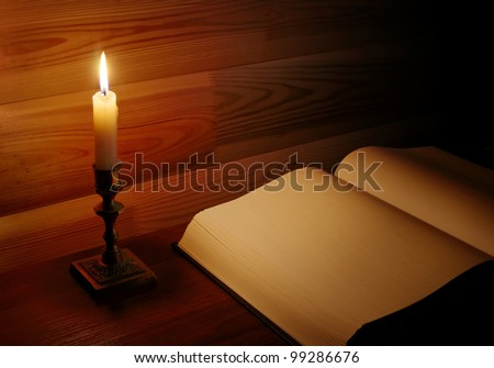 clear page of old opened book illuminated with candle