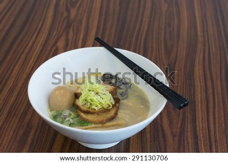 Clear ramen or yellow noodle soup with roasted marinated pork and whole egg.  Cooked with slices of bamboo shoot and Chinese black fungus.  Garnished with spring onion and fresh shredded vegetable. - stock photo