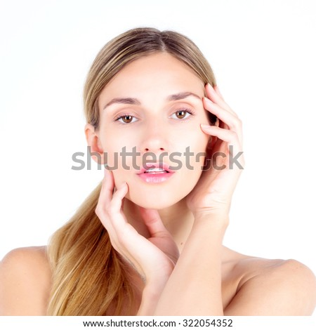 Clear skin. Beautiful woman looks at the camera and touching face with her hands. SPA and beauty