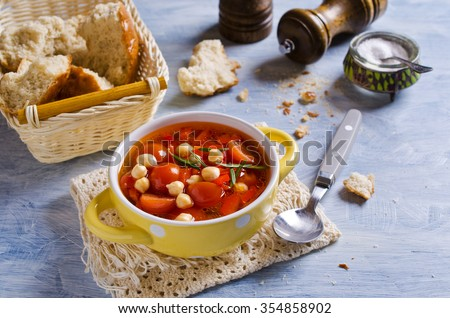 Clear soup with vegetables and chickpeas. Selective focus. - stock photo
