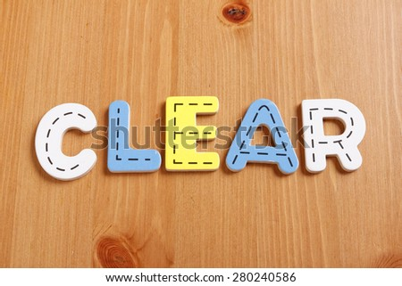 CLEAR, spell by woody puzzle letters with woody background