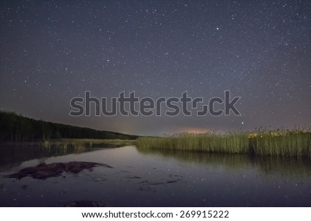 Clear starlit night on the river. Reflection of stars in the river in the starlit night. Starlit night on the river at the wood with reflection of stars in water. To make wishes. stars in the sky - stock photo