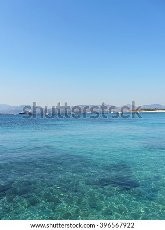 Clear turquoise sea water and boats on the horizon in summertime in Sardinia, Italy