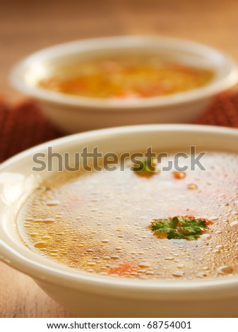 Clear vegetable soup close up. Shallow depth of field. - stock photo
