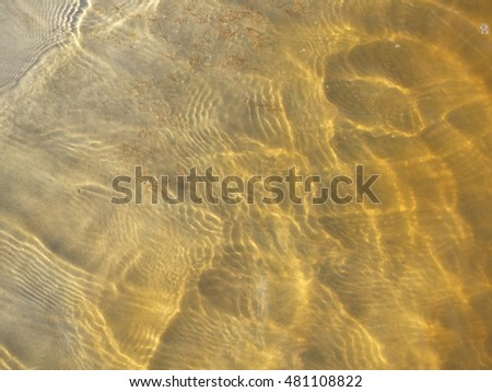 clear water above sand bottom with sunbeams