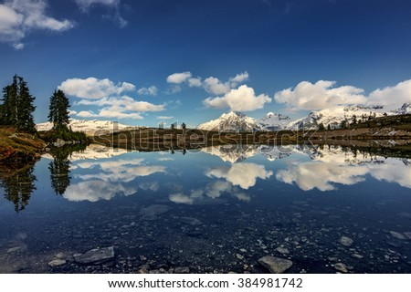 Clear water creating a vivid reflection of the snow-capped mountains and trees - stock photo