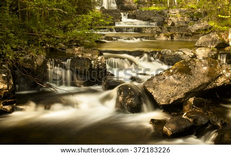 Clear water falling down in cascade deep in forest. Norwegian landscape. Tilt-shift lens long-time photography. - stock photo