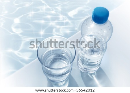 Clear Water glass and bottle with sparkling water on a swimming pool - stock photo