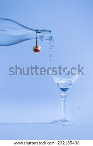 Clear water pour out of bottle splash into glass and spill with a blue back lighting - stock photo