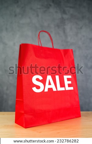 Clearance Sale Red Paper Shopping Bag on Wooden Retail Store Table. - stock photo
