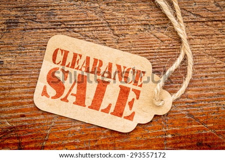 clearance sale sign a paper price tag against rustic red painted barn wood