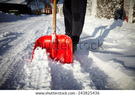 Clearing garden and road after a big snowstorm - stock photo
