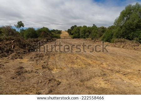 Clearing, grading, leveling and clearing of vegetation on land field for the construction of road or highway  - stock photo