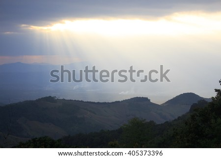 clearly horizon sunlight from cloud rays to green hill - stock photo
