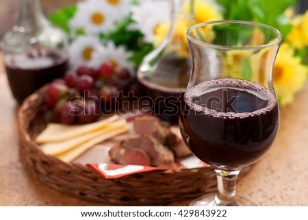 Clearly picture wine in the glass on the background of the products in a wicker tray. The kebab platter, cheese, ham, grapes. All combined with each other and creates appetite.