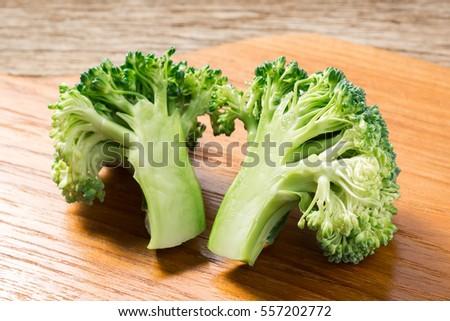 cleave broccoli on wooden chopping block on old wood table ( Brassica oleracea var., Cruciferae )