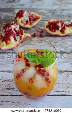 Clementine juice with pomegranate and mint leaves in a glass full of ice cubes - stock photo