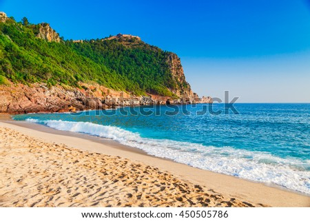 Cleopatra beach on sea coast with green rocks in Alanya peninsula, Antalya district, Turkey. Beautiful sunny landscape for tourism with clear water and sand. Alanya Castle on the cliff - stock photo