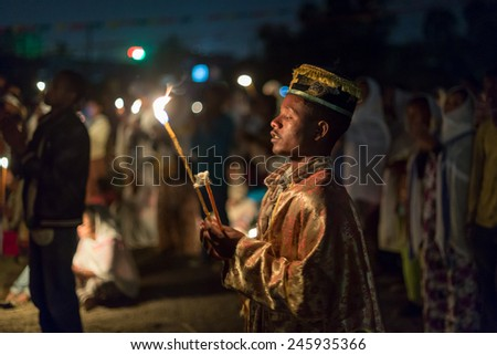 Clergy of the Ethiopian Orthodox Church holds a wax candle during the prayer ceremony of Timket, the Ethiopian Orthodox celebration of Epiphany, on January 19, 2015 in Addis Ababa. - stock photo