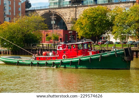 CLEVELAND - OCTOBER 11, 2014: The tugboat Iowa pulls an unseen lake freighter on the Cuyahoga River past the Suprerior Viaduct and downtown apartments on its way to Lake Erie and ports beyond. - stock photo