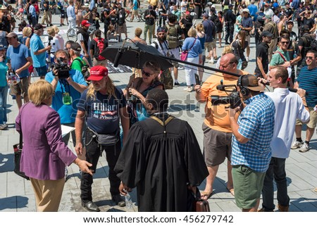 CLEVELAND, OH - JULY 20, 2016: A Trump supporter and a man in a purple jacket have a conversation on Public Square recorded by the media during the Republican National Convention. - stock photo