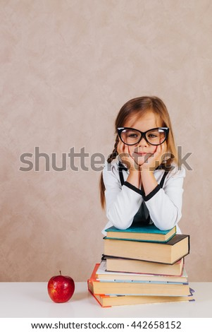 Clever and smartest little girl with textbooks and books back to school with a smile - stock photo