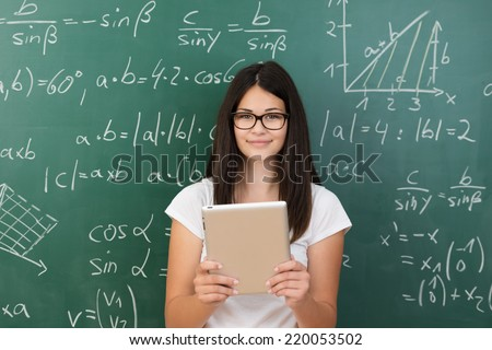 Clever attractive young female college student wearing glasses and holding a tablet computer in her hands standing in front of a chalkboard covered in equations in maths class smiling at the camera - stock photo