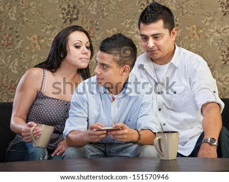 Clever Hispanic teenager watching parents watch his text messaging - stock photo