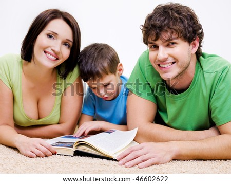 Clever preschool  boy reading book with his young happy smiling parents - stock photo