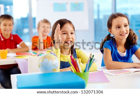 Clever schoolkids raising their hands to answer the question - stock photo