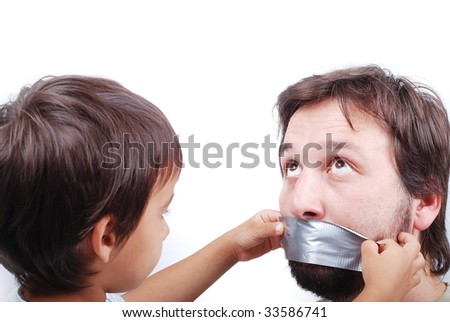 Clever son is putting a strip on father's mouth - stock photo