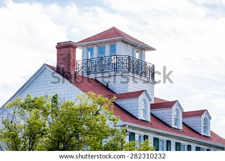 Cliassic white home with red roof, dormers and widows walk - stock photo