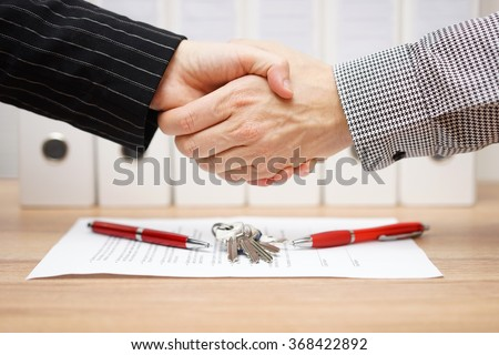 client and agent are handshaking over real estate contract and keys - stock photo