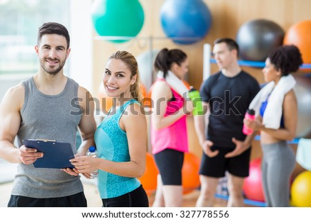 Client and trainer looking at clipboard at the gym - stock photo