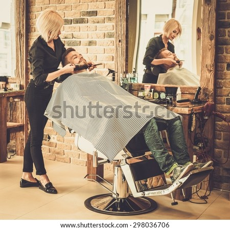 Client during beard and moustache grooming in barber shop - stock photo