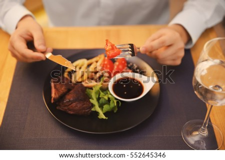Client eating tasty dish in restaurant, close up