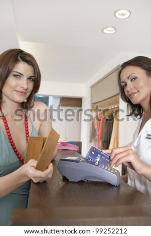 Client making payment at store's till with credit card. - stock photo