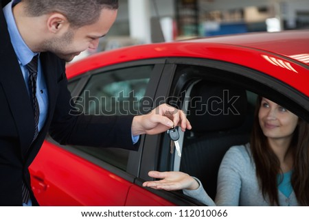 Client receiving car keys in a dealership - stock photo