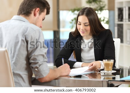 Client signing a document in an office with a businesswoman looking the contract - stock photo