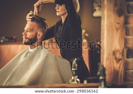 Client visiting hairstylist in barber shop - stock photo