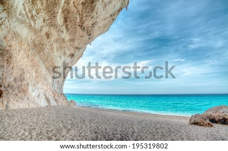 cliff and sand by a turquoise sea - stock photo