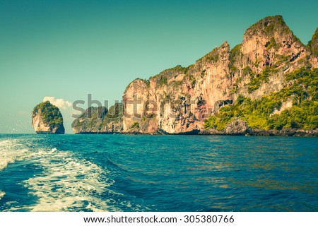 Cliff and the clear sea with a boat near Phi Phi island in south of Thailand - stock photo