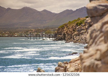 Cliff by the coast over the sea in sunset at summer - stock photo