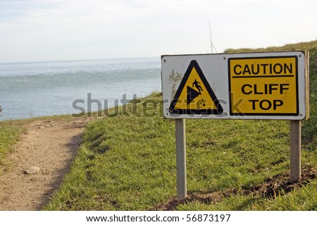 Cliff Edge warning sign Warning sign beside a footpath along the cliffs of Swanage, Dorset.  The chalk cliffs are gradually falling into the sea.  Just beyond the path is the English Channel. - stock photo
