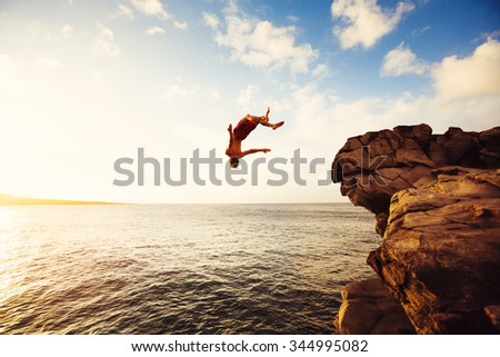 Cliff Jumping into the Ocean at Sunset, Outdoor Adventure Lifestyle - stock photo