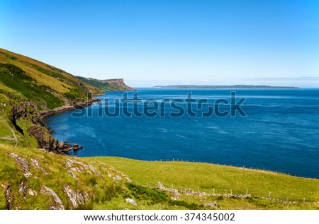 Cliffs on Northern Coast of Antrim County in Northern Ireland and Rathlin Island - stock photo