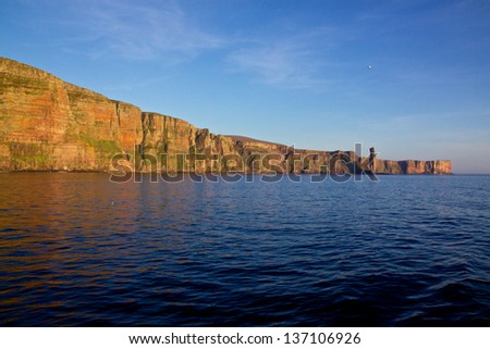 Cliffs with layers of red sandstone on the western coast of Orkney Islands - stock photo