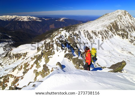 Climber above snow covered summits in fine winter day - stock photo
