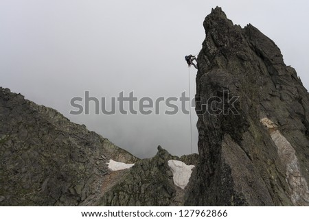 Climber abseiling from a vertical pillar in stormy weather - stock photo